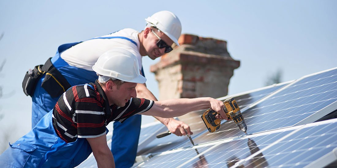 Portrait of successful technician showing thumb-up gesture standing in front of unfinished high exterior solar panel photo voltaic system blue shiny surface with team of workers on high platform.
